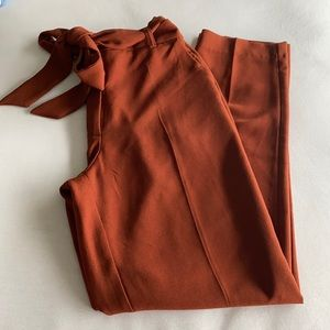 Burnt orange trousers with a tie belt and pockets.